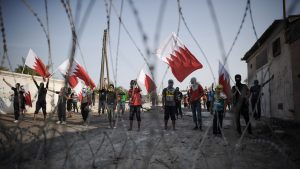 TOPSHOTS Bahraini protestors wave their ...TOPSHOTS Bahraini protestors wave their national flag as they stand behind barbed wire placed by riot police during demonstration against the ruling regime in the village of Shakhora, west of Manama, on August 14, 2013.. Bahraini police headed off a protest against Gulf kingdom's Sunni rulers that the Shiite-led opposition activists called for near the US embassy in defiance of a ban. The police deployment prevented protesters from reaching the spot designated by the Bahrain Rebellion Movement, Tamarod, for the main rally outside the US embassy in the capital Manama. AFP PHOTO/MOHAMMED AL-SHAIKHMOHAMMED AL-SHAIKH/AFP/Getty Images