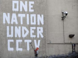 Street graffiti by elusive graffiti artist Banksy is seen on a wall, next to a CCTV camera, in central London November 25, 2008. REUTERS/Toby Melville (BRITAIN) - RTXAYIO